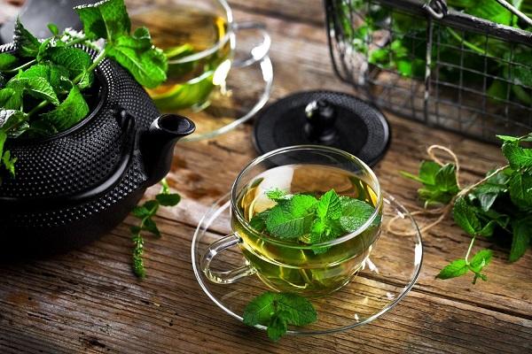 Fekete színű teáskanna, benne friss mentalevelek, mellette üveg teáscsészében mentatea és mentaágak.