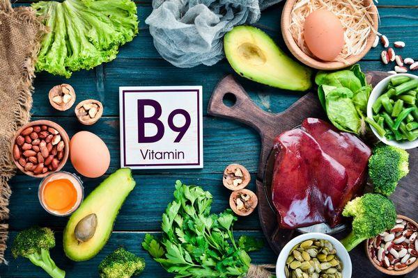 B9-vitamint tartalmazó élelmiszerek egy asztalon: tojás, avokádó, máj, bab, dió, mandula, brokkoli, zöldbab, petrezselyem, saláta.