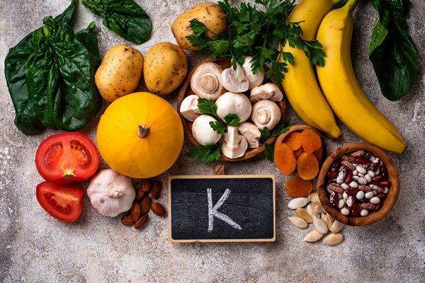K-vitaminban gazdag ételek egy asztalon: spenótlevelek, burgonya, gomba, banán, bab, tökmag, sárgabarack, mandula, fokhagyma, paradicsom.