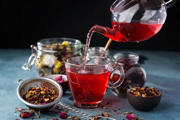 Üveg teáskannából piros gyümölcsteát öntenek egy üvegpohárba, mellette gyümölcstea tálban és teaszűrőben.