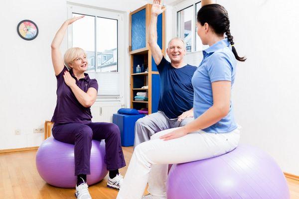 Tornateremben idős házaspár fitneszlabdán ülve tornázik gyógytornász vezetésével.