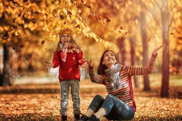 Ősszel az erdőben avaron ülve sárguló leveleket dobál anya és lánya.