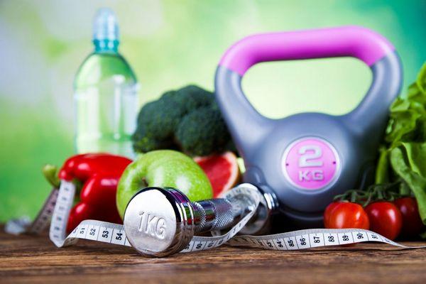 Fogyókúra kellékei, súlyzók, mérőszalag, valamint brokkoli, paprika, paradicsom, saláta, alma, vizespalack.