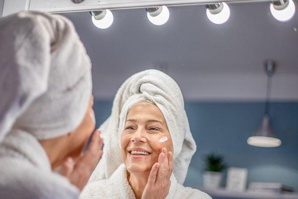 Mosolygós idős hölgy a tükör előtt arcát krémmel keni, fején fehér törölköző.