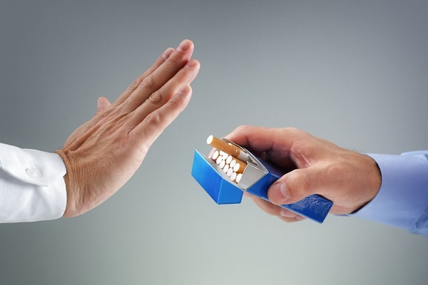 Két kéz egymással szemben, az egyik cigarettásdobozt nyújt, a másik nemet int neki.