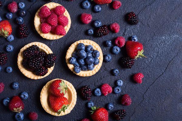 Bogyós gyümölcsök, eper, málna szeder, fekete áfonya egy asztalon, illetve kerek sütemények tetején.