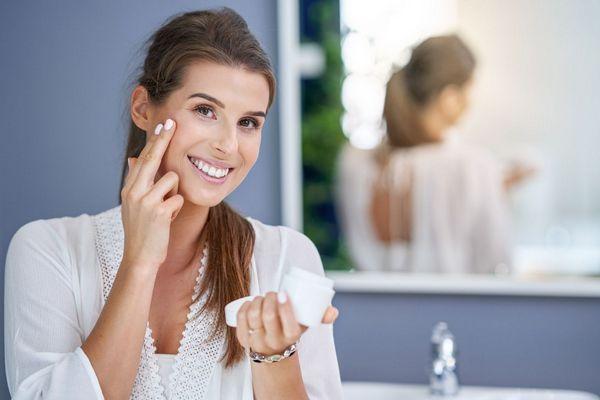 Fiatal hölgy a fürdőszobában arckrémmel keni az arcát.