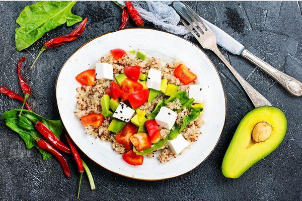 Koleszterinszintet csökkentő élelmiszerek, avokádó, bulgur, paprika, spenót, quinoa, feta sajt egy tányéron, mellette villa és kés.