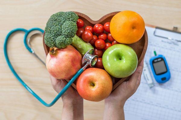 Szívalakú tálban brokkoli, gránátalma, almák, paradicsom és narancs, mellette fonendoszkóp, vércukorszintmérő és jegyzetfüzet.