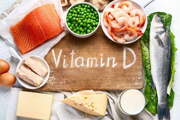 D-vitamint tartalmazó élelmiszerek egy asztalon, tojások, tej, hal, lazac, rák, sajtok, zöldborsó, gombák.