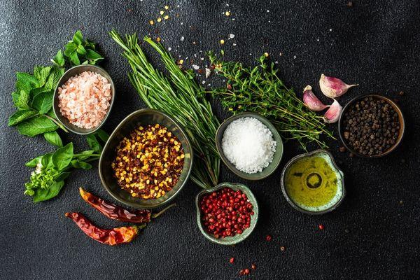 Egy asztalon elhelyezett fűszerek, bazsalikom, oregánó, rozmaring, fekete bors, őrölt piros paprika, chilipaprika, himalája só, tengeri só, olívaolaj.