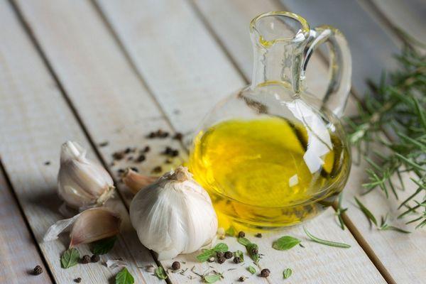 Egy asztalon üvegben fokhagymaolaj, mellette fokhagymák és rozmaringlevelek.