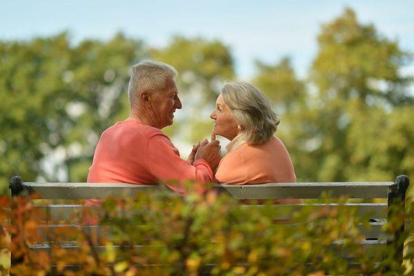Időskorú házaspár egy parkban padon ülve beszélget.