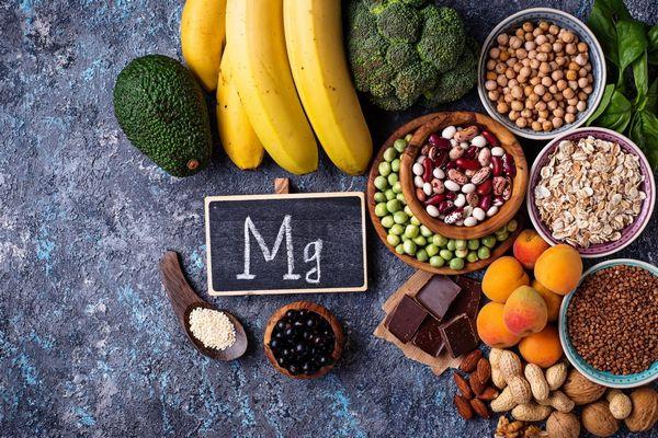 Magnéziumot tartalmazó élelmiszerek egy asztalon, banán, avokádó, brokkoli, bab, lencse, étcsokoládé, mandula, földimogyoró, mandula, zabpehely, spenót, kajszibarack, szezámmag, csicseriborsó.