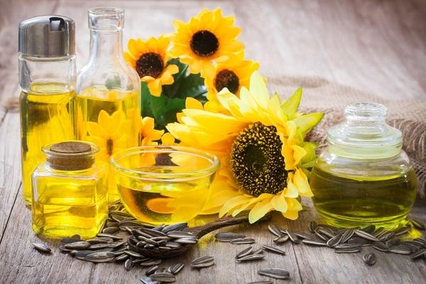 Egy asztalon napraforgómagok, napraforgóvirágok, mellettük üvegekben napraforgóolaj.