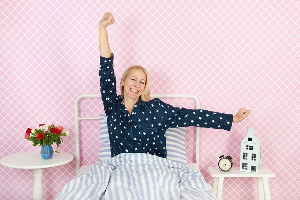 Középkorú hölgy felébredve az ágyban tornázik.