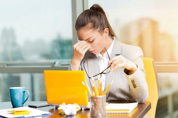 Fiatal hölgy az irodában laptopjával dolgozik, fejét a kezével támasztja a fáradtság és a stressz miatt.