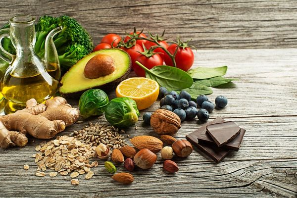 Egy asztalon elhelyezett gyömbér, mandula, mogyoró, kelbimbó, citrom, avokádó, spenót, paradicsom, brokkoli, dió, pisztácia, étcsokoládé.