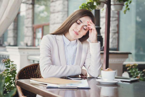 Fiatal hölgy kávézás közben a fáradtsága miatt az asztal fölé hajol, kezével támasztja a fejét.