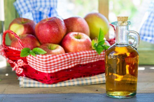 Egy piros kosában sok alma, mellette almaecet egy üvegben.