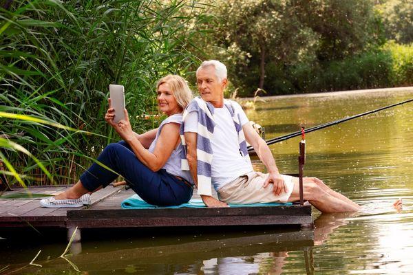 Középkorú házaspár vízparton egy stégen ülve horgászik.