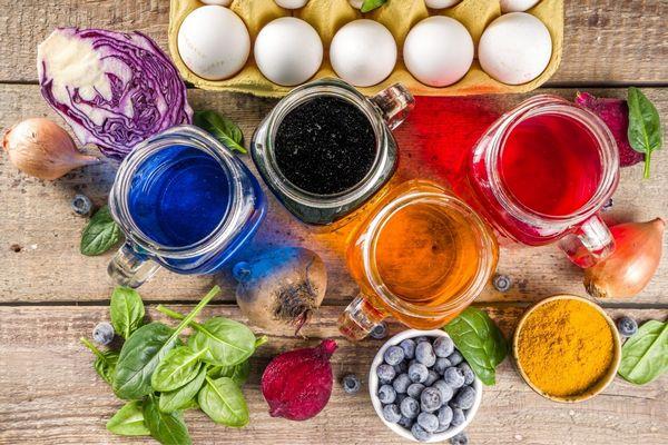 Tojások tojástartóban, mellette természetes ételszínezékekre használható növények, többek között lila káposzta, hagyma, spenótlevelek, cékla, fekete áfonya, kurkuma és üvegekben színes folyadékok.