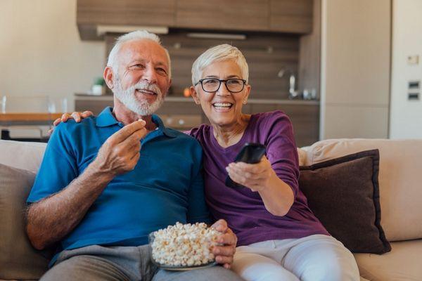 Idős házaspár otthonában tévét néz, közben pattogatott kukoricát eszik.