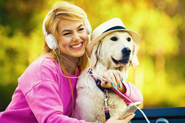 Fiatal lány az erdőben a kutyájával pihen, fejhallgatóval zenét hallgat.