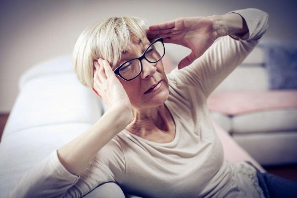 Idős hölgy a kanapén ül, két kezével a fájós fejét fogja.
