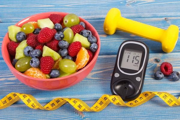 Kék színű asztalon piros tál, benne gyümölcsök, mellette sárga kézi súlyzó, mérőszalag és vércukorszintmérő.