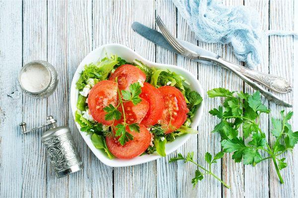 Egy asztalon szív alakú tányérban saláta, paradicsom, sajt és petrezselyem, mellette petrezselyemzöld, kés és kanál, illetve fűszermalom.