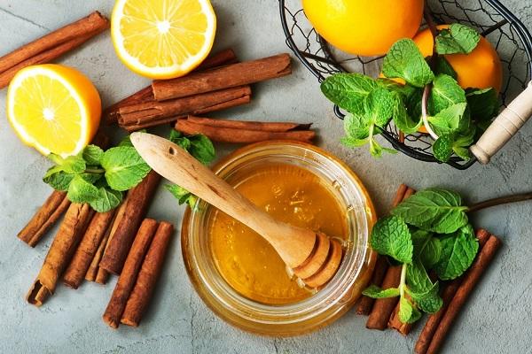 Egész és félbevágott narancsok, fahéjdarabok, citromfűágak egy asztalon, mellettük egy üvegben méz.