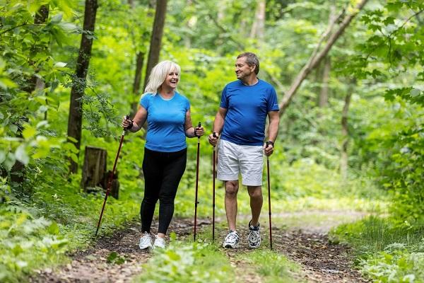 Középkorú házaspár az erdőben sétál, kezükben túrabot.