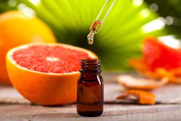 Félbevágott grapefruit egy asztalon, mellette üvegcsében grapefruitmag-olaj.