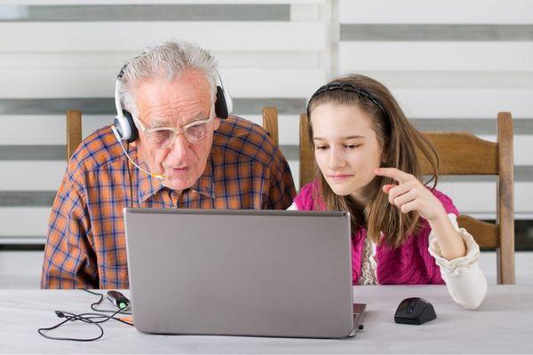 Nagypapának az unokája tanítja a laptop használatát.