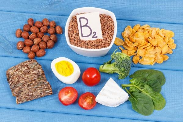 B2-vitamint tartalmazó élelmiszerek egy asztalon: mogyoró, tojás, paradicsom, gabonapehely, brokkoli, spenót, sajt, teljes kiőrlésű kenyér és hajdina.