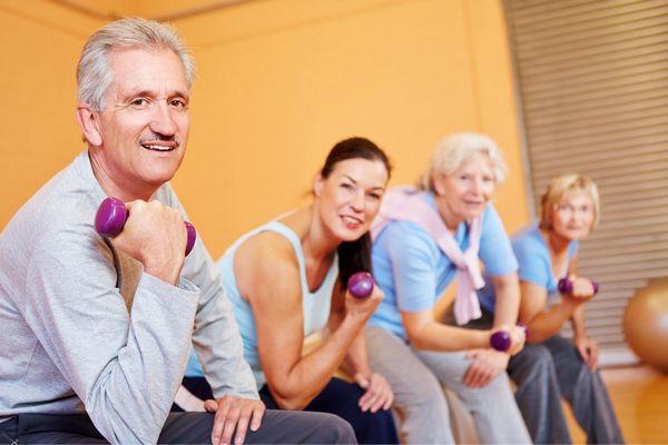 Nyugdíjas férfi és és középkorú hölgyek egy tornateremben súlyzóval a kezükben edzenek.