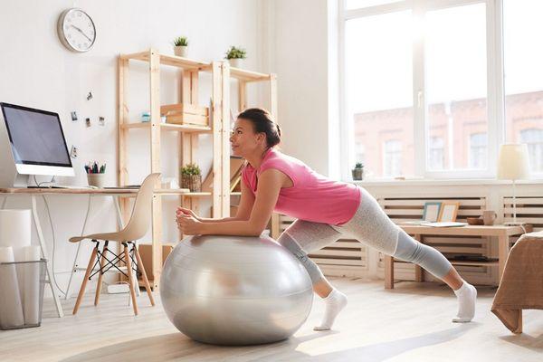 Fiatal hölgy otthonában fitnesslabdával tornázik.