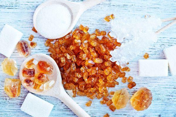 Fehér cukor, kockacukor és barna cukor egy asztalon.