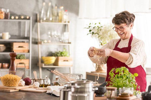 Idős hölgy a konyhában tésztát főz.
