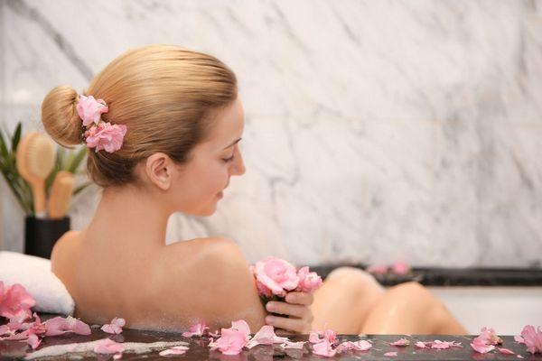 Fiatal hölgy fürdőkádban fürdik, hajában és a kád szélén virágszirmok vannak elhelyezve.