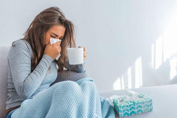 Az otthonában allergiás tünetektől szenvedő, orrot fújó lány.