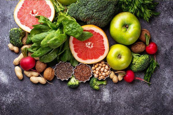 Egészséges élelmiszerek egy asztalon, félbevágott grapefruit, almák, brokkoli, spenótlevelek, retek, földimogyoró, lenmag, chiamag, dió és csicseriborsó.