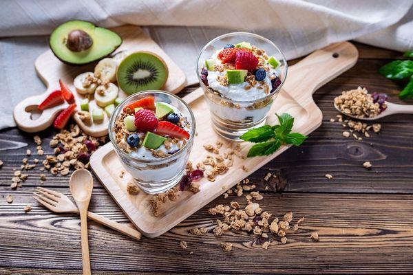 Egy asztalon müzli, magvak és gyümölcsök, kivi, banán, eper és avokádó, mellettük üvegpoharakban joghurt megszórva gyümölcsökkel és müzlivel.