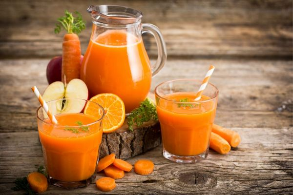 Egy asztalon sárgarépák, félbevágott alma és narancs, mellettük üvegkancsóban és üvegpoharakban sárgarépalé.