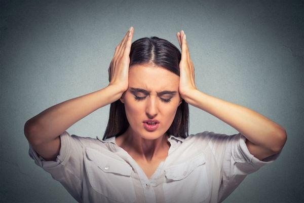 Fiatal hölgy két kezével fogja a stressztől fájó fejét.