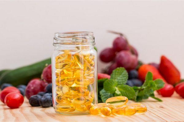 Vérnyomáscsökkentő ételek egy asztalon, halolajkapszulák egy üvegben, mellette mentalevél, fekete áfonya, eper, som, retek és uborka.