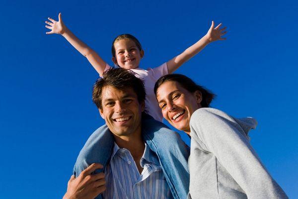 Mosolygó család, apa, anya és kislányuk, aki az apukája nyakában ülve a magasba emeli a kezeit.