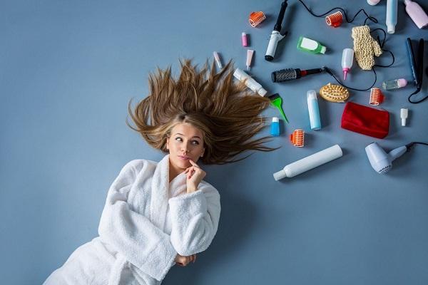 Fiatal lány köntösben fekszik kibontott hajjal, mellette hajápolási termékek, sampon, hajkefe, hajszárító, hajcsavaró, hajbalzsam.