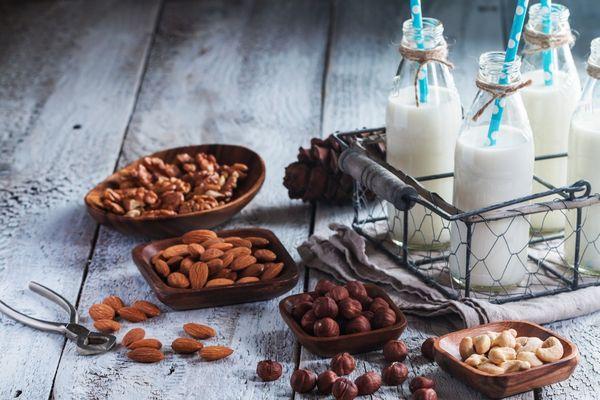 Egy asztalon tálakban magvak, mandula, mogyoró, dió, mellettük üvegekben tej kék szívószálakkal.